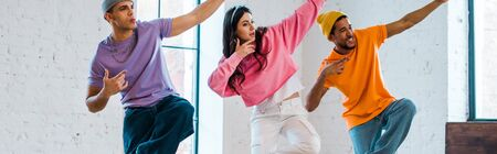 panoramic shot of young woman and stylish multicultural men breakdancing