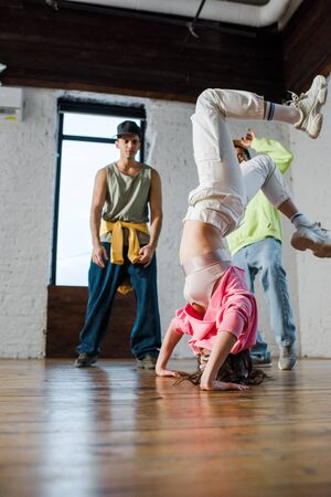 selective focus of girl doing handstand while breakdancing near multicultural men Stock Photo