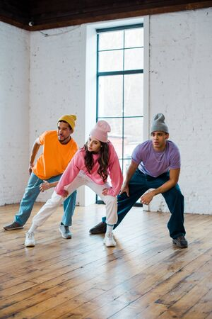 stylish and young multicultural dancers in hats breakdancing Stock Photo