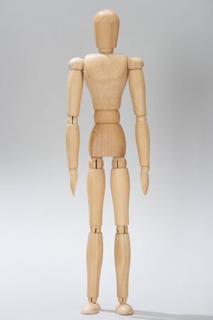 Wooden doll with hinges on grey background