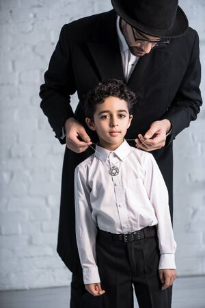 handsome jewish father wearing star of david necklace on son