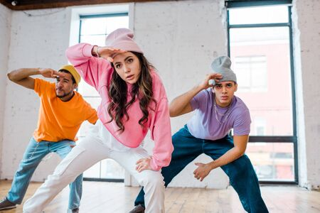 selective focus of stylish girl breakdancing with multicultural men in hats