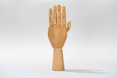 Wooden hand with shadow on grey background