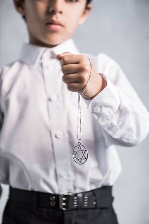 cropped view of jewish boy in shirt holding star of david necklace 版權商用圖片