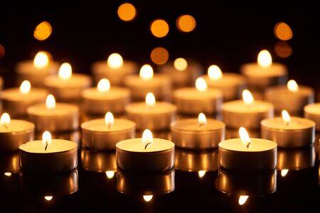 fuoco selettivo di candele accese che brillano nell'oscurità con luci bokeh