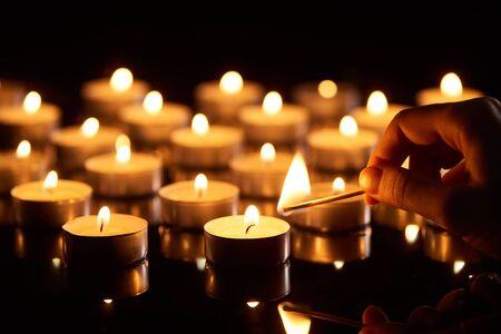 messa a fuoco selettiva della donna che accende candela con fiammifero al buio