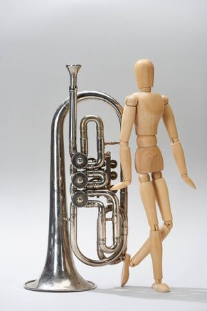 Alto horn with wooden puppet on grey background