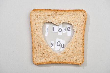 Top view of bread slice with carved heart shape and i love you lettering on grey background