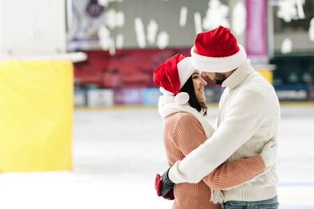 beautiful couple in santa hats spending time on skating rink Banque d'images
