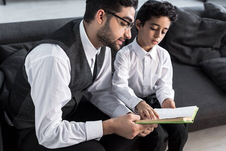 handsome jewish father and son reading book in apartment Standard-Bild
