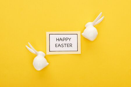 top view of greeting card with happy Easter lettering near Easter white bunnies on yellow colorful background