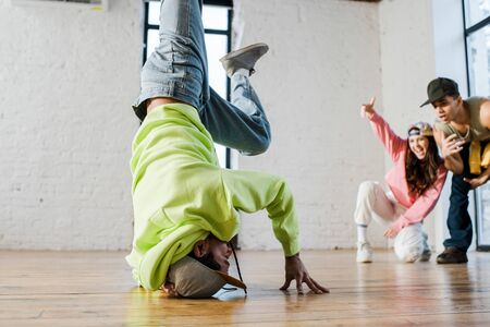 selective focus of african american dancer breakdancing near emotional man and woman