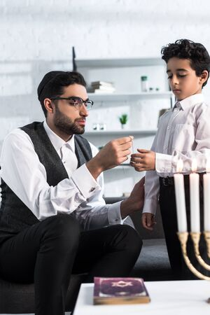 jewish father giving necklace to cute son in apartment