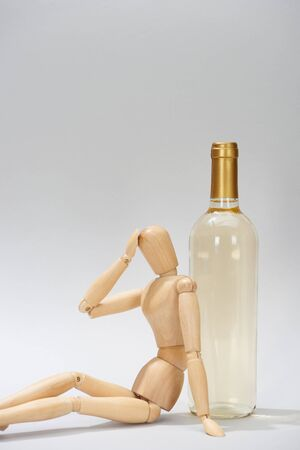 Wooden doll with hand by head beside wine bottle on grey background Stock Photo