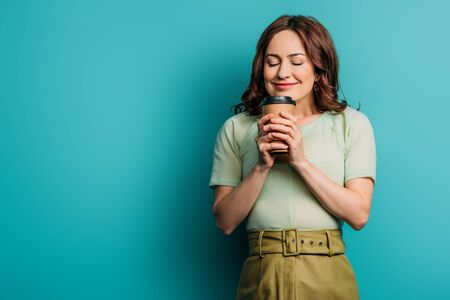 smiling, pleased girl holding coffee to go on blue background