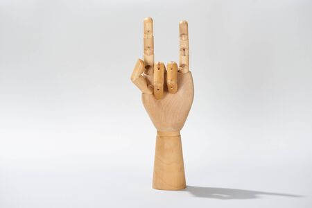 Wooden hand with rock sign on grey background Stock Photo