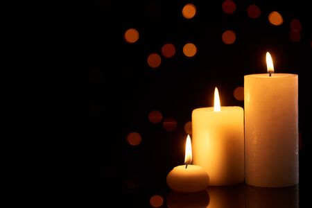burning candles glowing in dark with bokeh lights on background