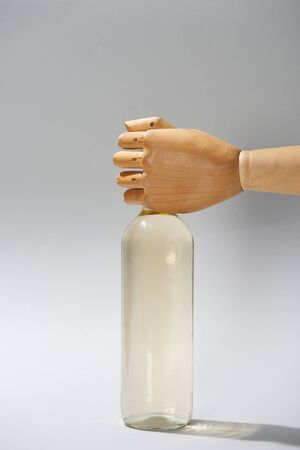 Wooden hand of dummy with bottle of wine on grey background Stock Photo
