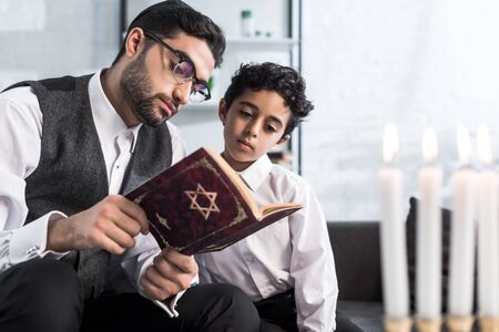 handsome jewish father and son reading tanakh in apartment