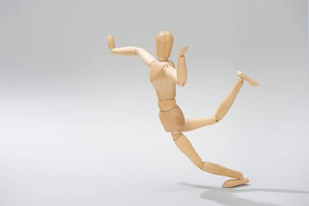 Wooden doll with raised hands and leg on grey background