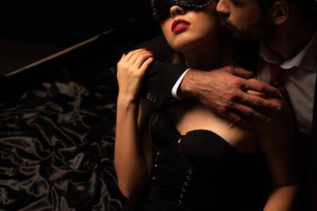 vista ritagliata dell'uomo che abbraccia la donna in maschera sul letto in una stanza buia Archivio Fotografico