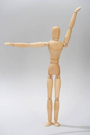 Wooden puppet with raised hands on grey background