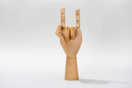 Wooden hand of puppet with rock gesture on grey background Stock Photo