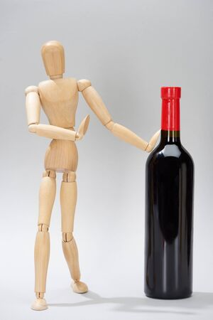 Wooden doll with bottle of red wine on grey background Stock Photo