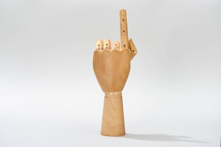 Wooden hand of puppet pointing with finger on grey background Stock Photo
