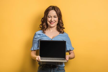 cheerful woman winking while holding laptop with blank screen on yellow background