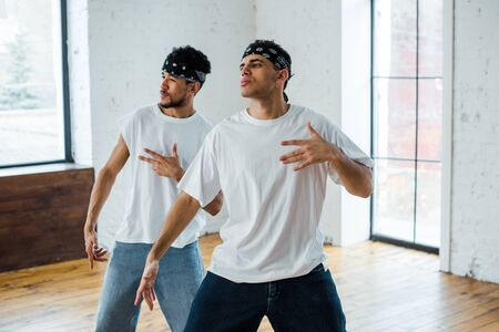 handsome multicultural dancers in headbands gesturing and posing while dancing hip-hop