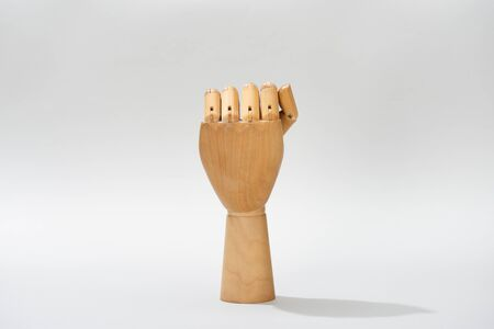 Hand of wooden doll with shadow on grey background Stock Photo