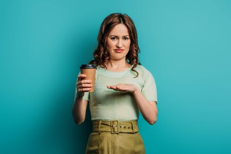 displeased woman showing refusal gesture while holding coffee to go on blue background Stok Fotoğraf - 137726126