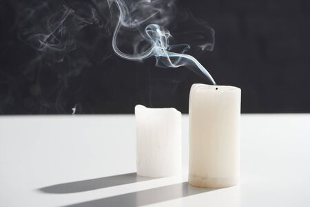 extinct white candles with smoke on black background
