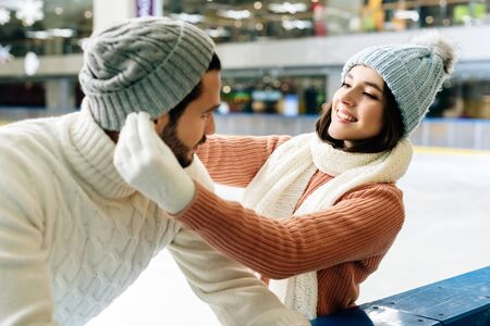 young smiling couple wearing hats on skating rink