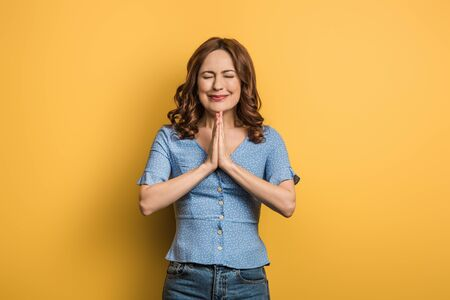 anxious girl showing praying hands with closed eyes on yellow background Reklamní fotografie