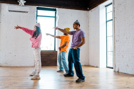 side view of attractive girl gesturing while breakdancing with handsome multicultural men in hats Stok Fotoğraf