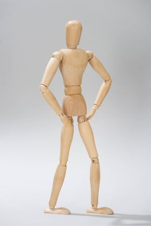 Wooden puppet with akimbo pose on grey background
