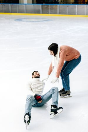positive young couple skating together while man falling on rink