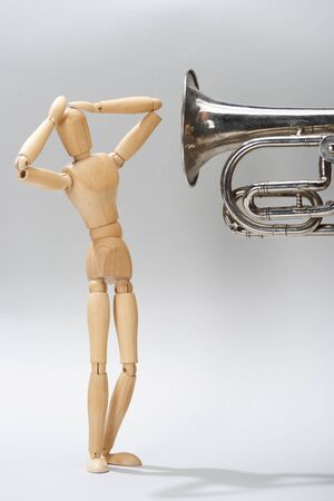 Wooden puppet with hands by head and alto horn on grey background Stock Photo