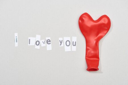 Top view of i love you lettering with red balloon on grey background Stock fotó