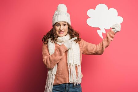 shocked girl in warm hat and scarf pointing with finger at thought bubble on pink background Stok Fotoğraf - 137725953