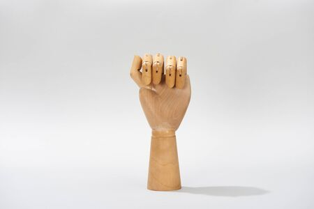 Hand of wooden doll in fist on grey background