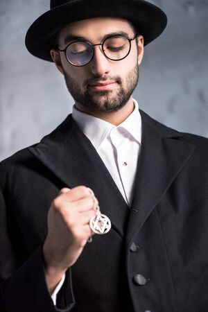 handsome jewish man in glasses holding star of david necklace