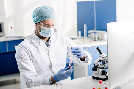 실험실에서 DNA 검사를 하는 백의를 입은 유전 컨설턴트