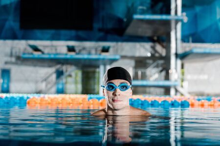 swimmer in googles and swimming cap looking at camera