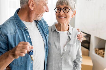 Ausgeschnittene Ansicht eines lächelnden Mannes, der Schlüssel hält und Frau im neuen Haus ansieht