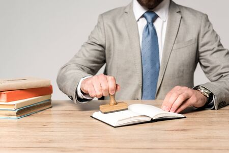 partial view of lawyer putting stamp in notebook isolated on grey