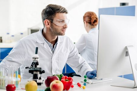 molecular nutritionist in white coat using computer in lab