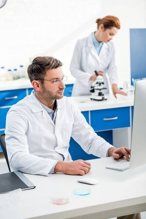 selective focus of molecular nutritionist using computer and his colleague using microscope on background